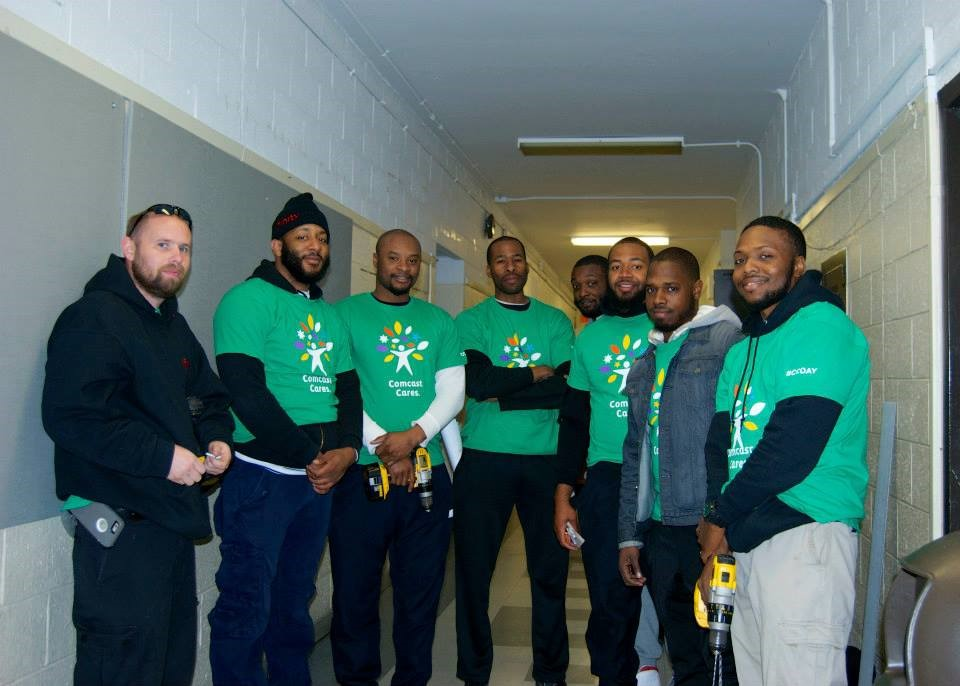 This crew of Comcast engineers led by Chris Powell installed fabric-covered panels along the first-floor hallway wall, repainted that wall, and then kept working to repaint the doors in the courtyard.