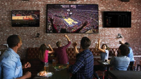 group of people watching sports on a tv