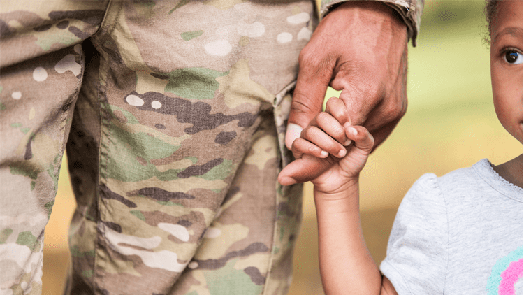 A member of the armed forces holds a child's hand.