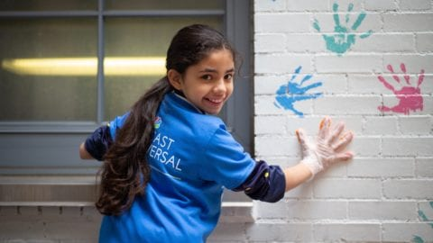 Little girl stamping her hand on a wall with paint