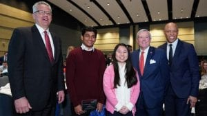 Two college students being honored by employees and local officials.