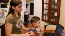 A mother and child use a laptop to video call a relative